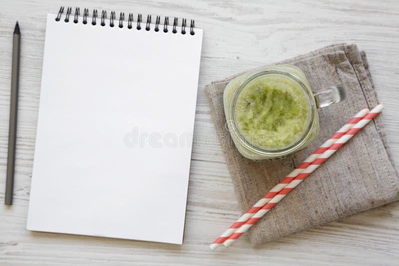 Zielony selerowy smoothie w szklanym słoju, pusty notepad z ołówkiem nad białym drewnianym tłem, odgórny widok Koszt stały, miesz zdjęcia stock