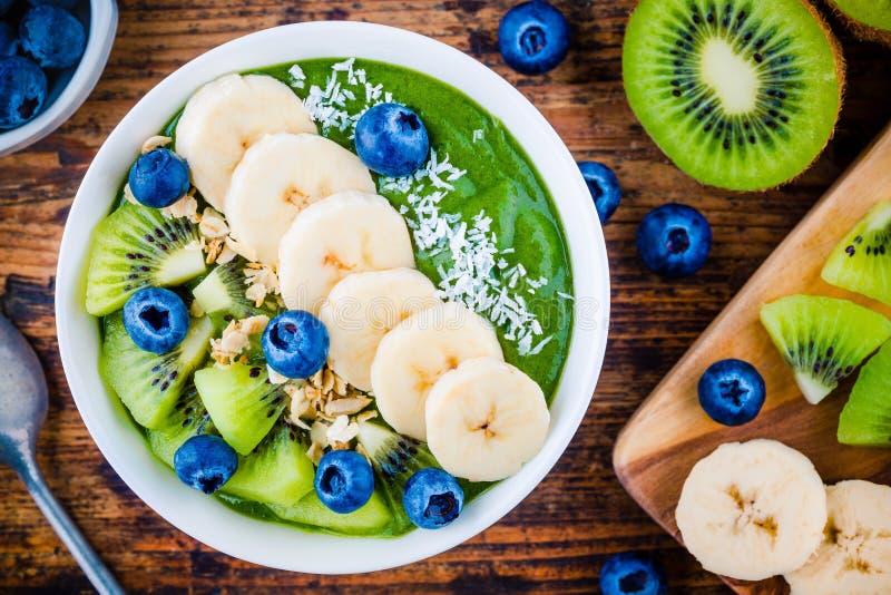 Zielony smoothie puchar z bananem, kiwi, czarną jagodą, granola i koksem, obraz royalty free