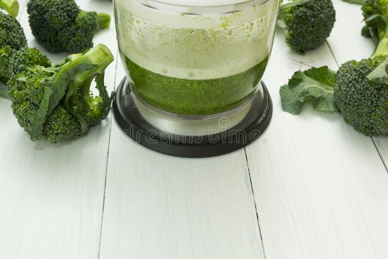 Zielony smoothie w surowych brokułach na drewnianym tle i blender Przestrzeń dla teksta obraz stock
