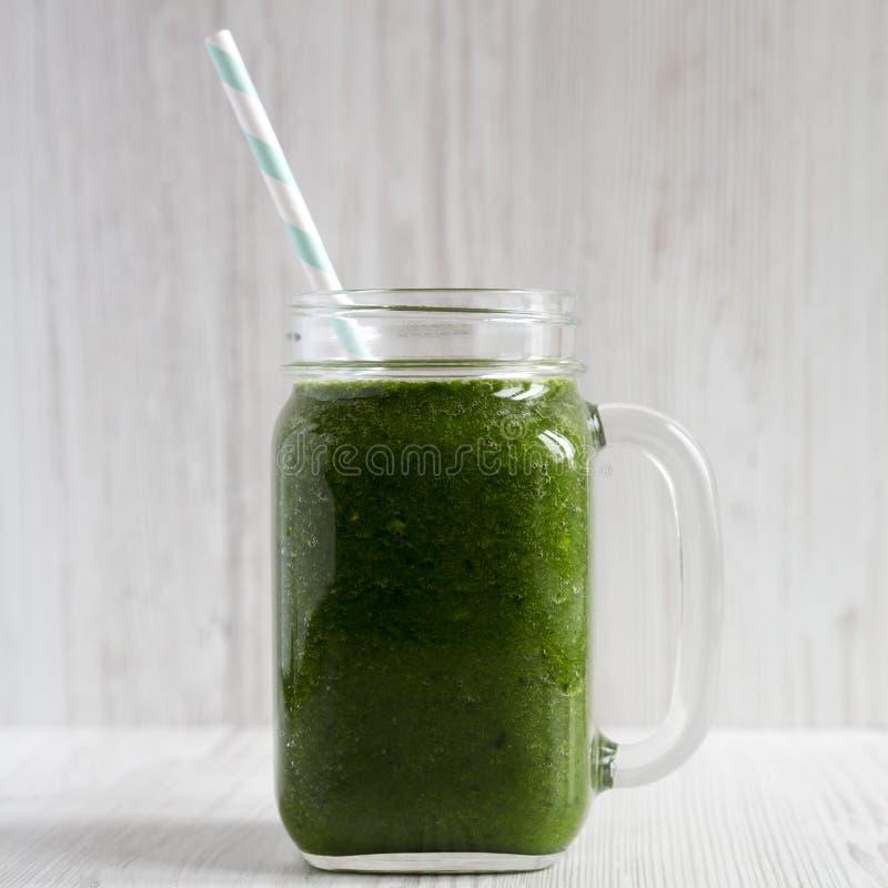 Zielony smoothie z avocado, szpinakami i bananem w szklanym s?oju nad bia?ym drewnianym t?em, boczny widok Zako?czenie zdjęcie stock