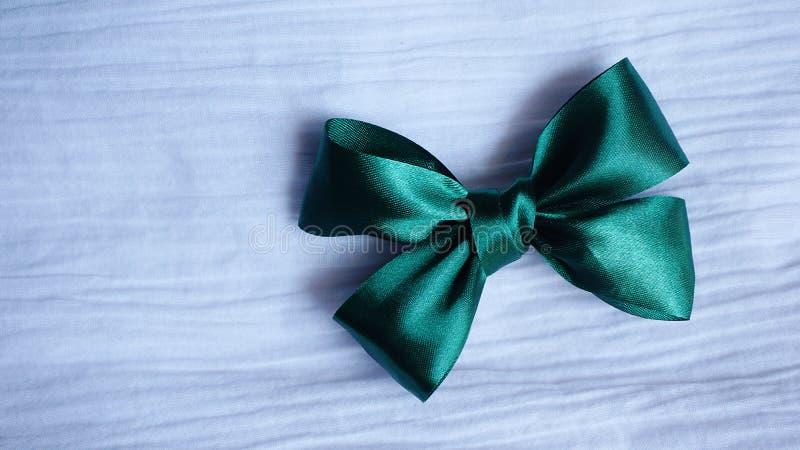 Zielony tasiemkowy łęk na białym tkaniny tle zdjęcie royalty free