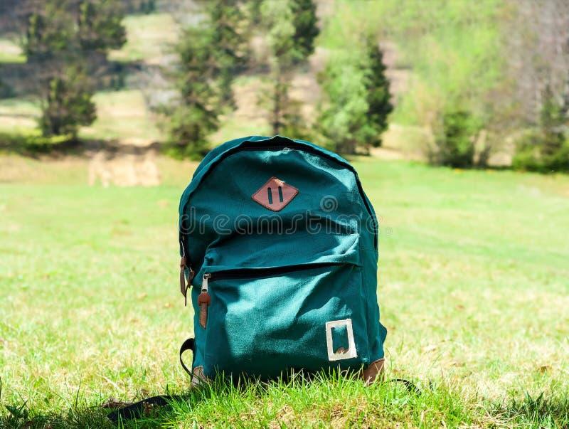 Zielony turystyczny plecak na gazonu tle w górach Podróży pojęcie w dzikim zdjęcie stock