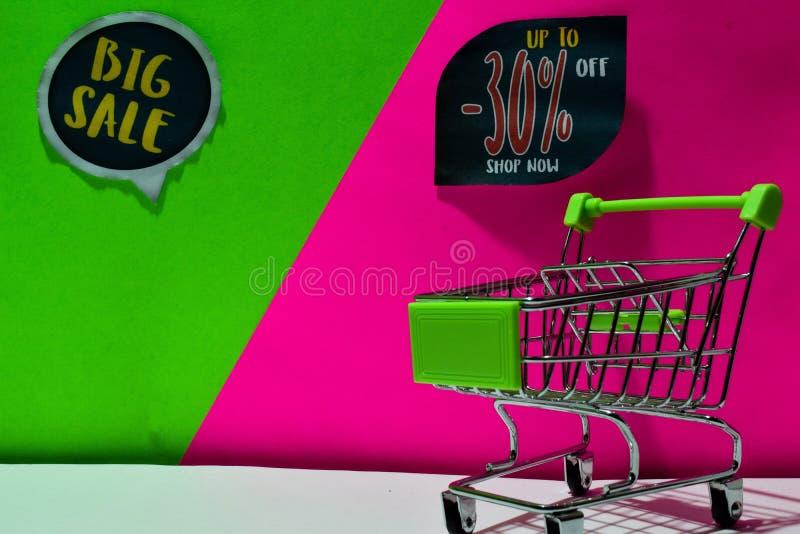 Zielony wózek na zakupy dołączająca Duża sprzedaż Do -30%, Sklepowego teksta na zieleni i menchii tła i Daleko, Teraz zdjęcie stock