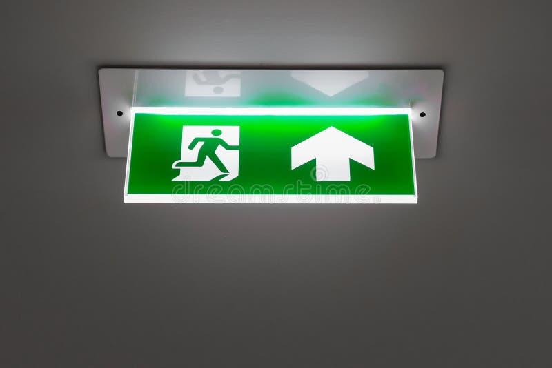 Zielony wyjście ewakuacyjne znak pokazuje sposób uciekać obrazy stock