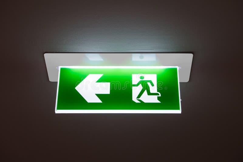 Zielony wyjście ewakuacyjne znak pokazuje sposób uciekać fotografia stock