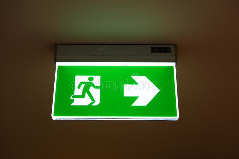 Zielony wyjście ewakuacyjne znak pokazuje sposób uciekać zdjęcie stock