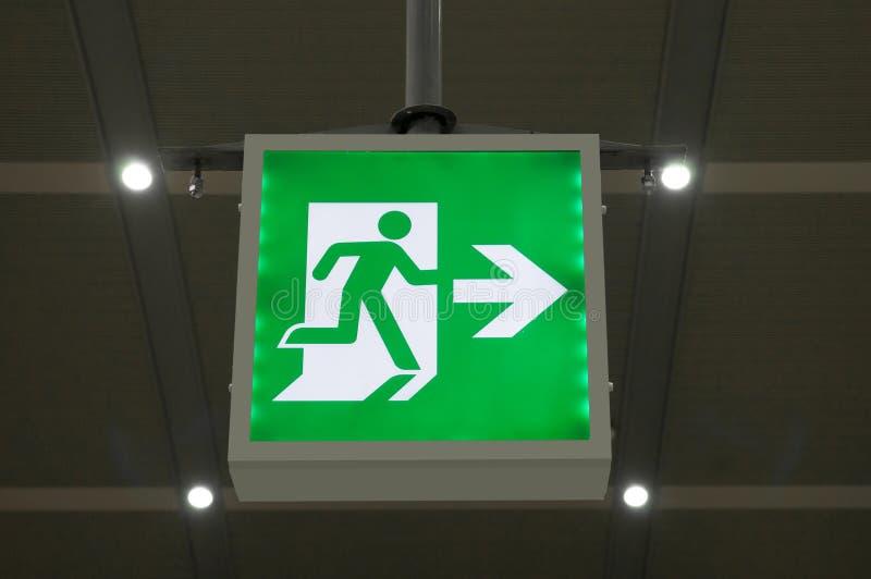 Zielony wyjście ewakuacyjne znak pokazuje sposób uciekać zdjęcie royalty free