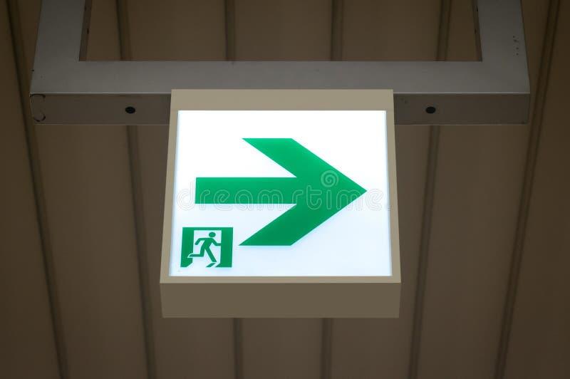 Zielony wyjście ewakuacyjne znak pokazuje sposób uciekać zdjęcia stock