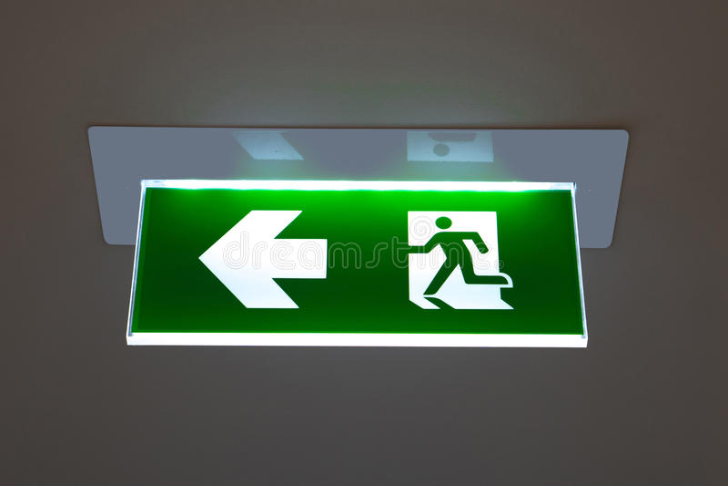Zielony wyjście ewakuacyjne znak pokazuje sposób uciekać obraz royalty free