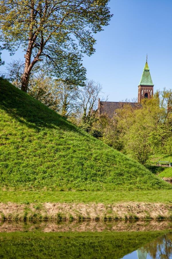 zielony wzgórze i drzewa odbijający w behind spokój wodzie i pięknym starym pałac, zdjęcie royalty free