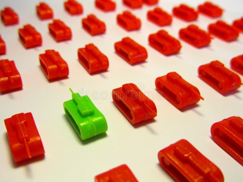 Zielony zabawkarski zbiornik naprzeciw rz?d?w czerwieni zabawki zbiorniki symbolizowa? Brexit i politycznego zderzenie zdjęcie stock