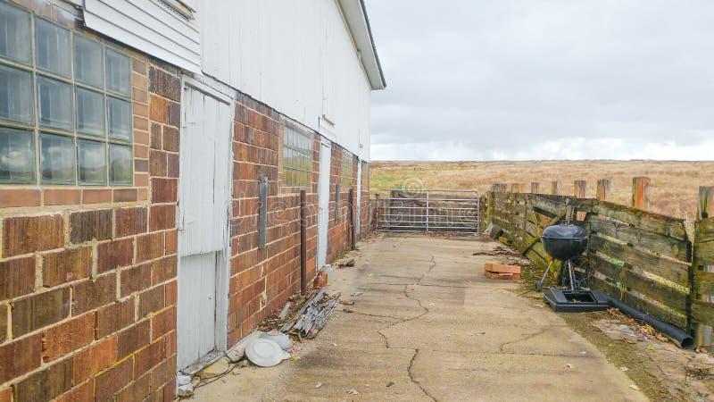 Ziemia uprawna z fechtunkiem, grillem i ceglanym domem, fotografia royalty free