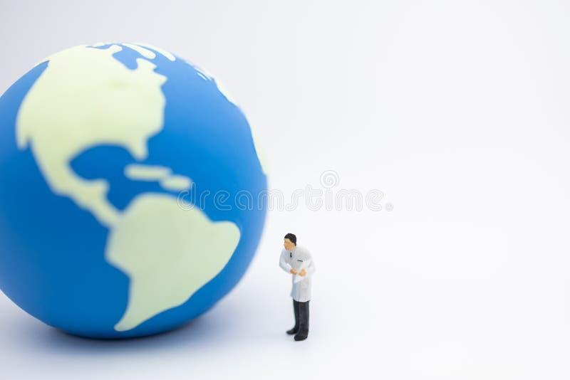Ziemska opieka, pojęcie, opieki zdrowotnej i środowiska Zamyka w górę lekarki miniatury postaci ludzi stoi i pokazuje mapa schowe obraz royalty free