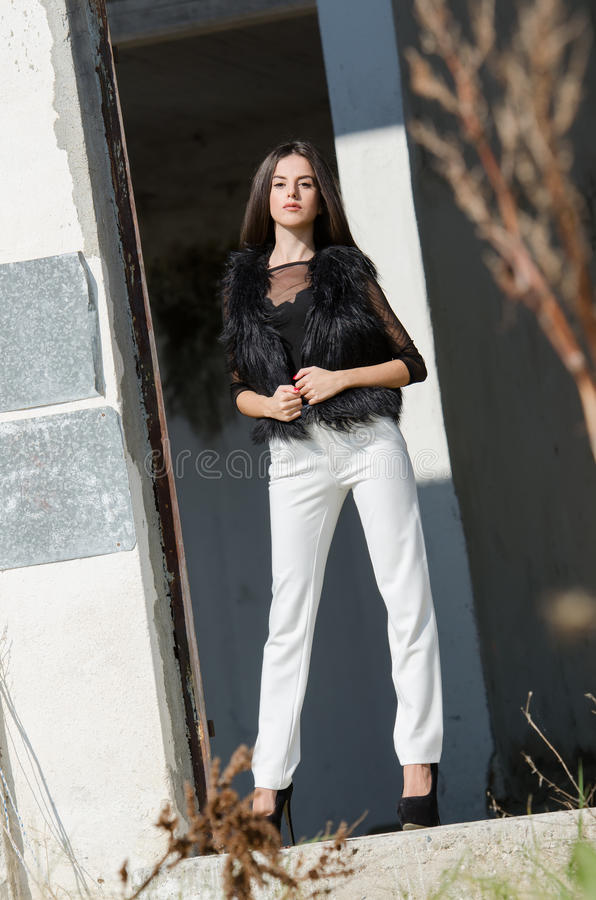 Zierliche junge Frau mit sehr langen Haarabnutzungsfersen und weißen Hosen stockbilder