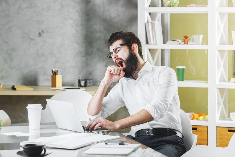 Ziewać męczącego mężczyzna przy pracą obraz stock