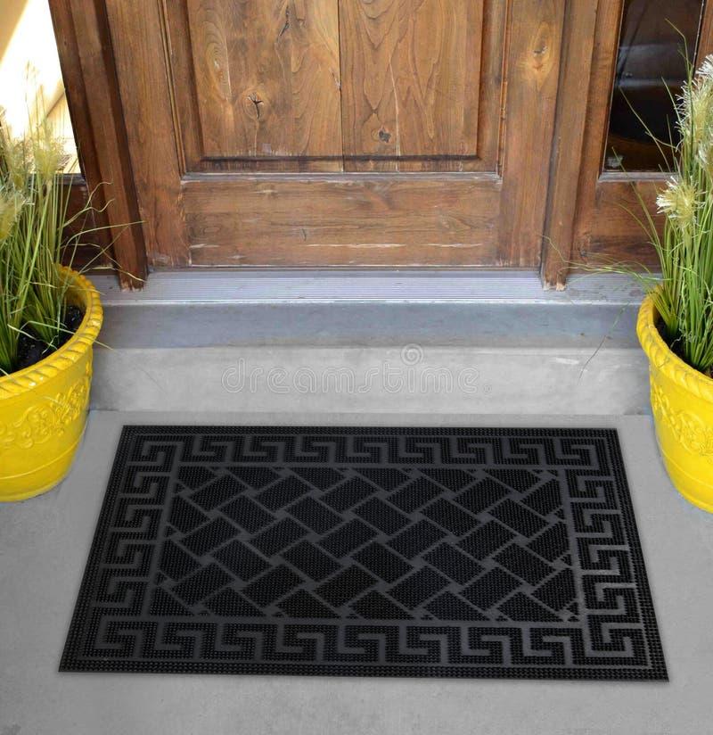 Zig-zag élégant noir modelé avec le tapis de porte d'entrée d'accueil de frontière de motif avec les fleurs et les feuilles jaune photographie stock libre de droits