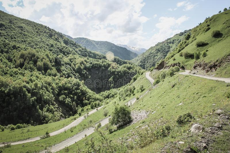 Zig Zag path in the caucasus mountains in Georgia. Dirt road to hiking. And clouds stock photography