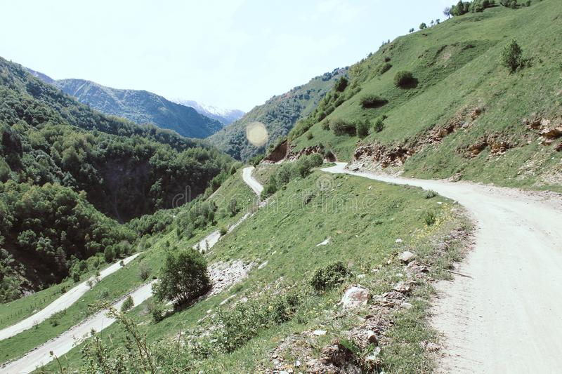 Zig Zag path in the caucasus mountains in Georgia. Dirt road to hiking. And clouds nature glacier trail hills tourists footpath sports pure greater snow pass stock image
