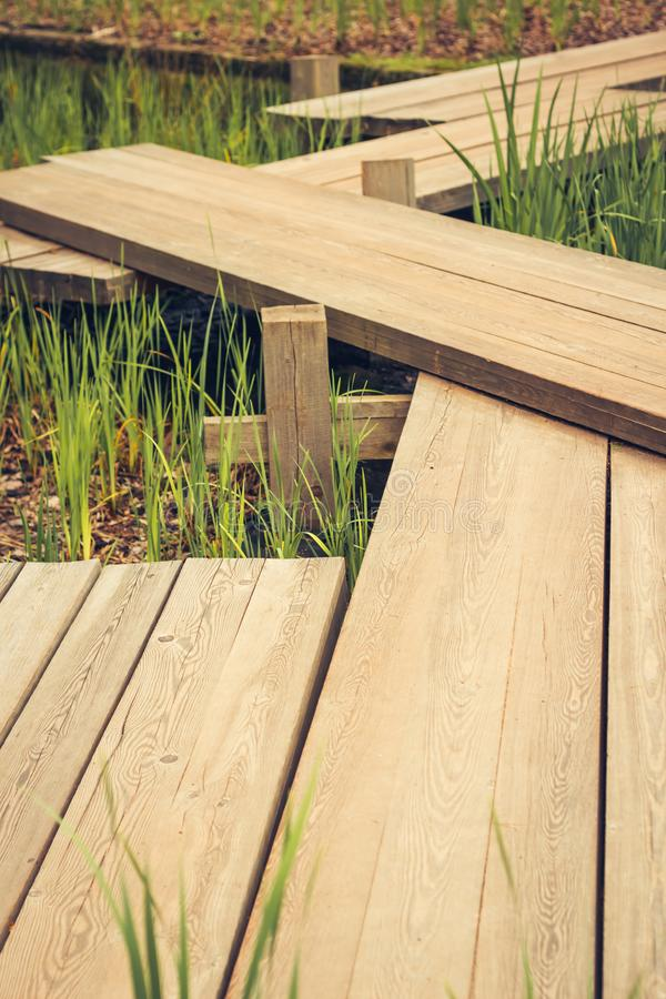 Zig-zag wooden pathway, footpath bridge over a lily pad filled water pond. Zig-zag pattern wooden pathway, footpath bridge over a lily pad filled water pond royalty free stock images