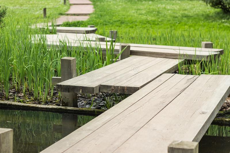 Zig-zag wooden pathway, footpath bridge over a lily pad filled water pond. Zig-zag pattern wooden pathway, footpath bridge over a lily pad filled water pond royalty free stock photography