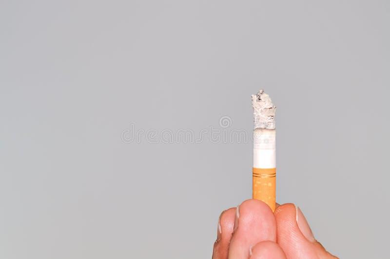Zigarette auf grauem Hintergrund stockbild