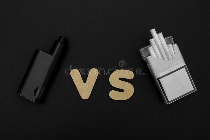 Zigaretten gegen Vape Elektronische Zigarette über einem dunklen Hintergrund Populäre Geräte des Jahres - modernes vaping Gerät stockbilder