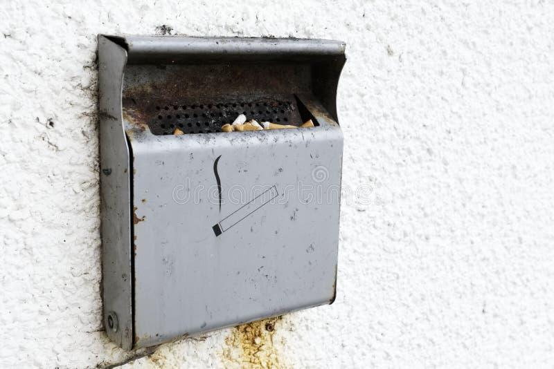Zigarettenraucher verboten Aschenbecher draußen asphaltieren auf Wandwand-Raumhintergrund stockbilder