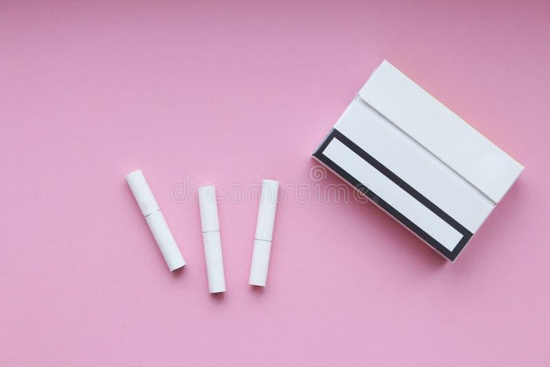 Zigarettenstöcke und -satz auf rosa Hintergrund stockfotos