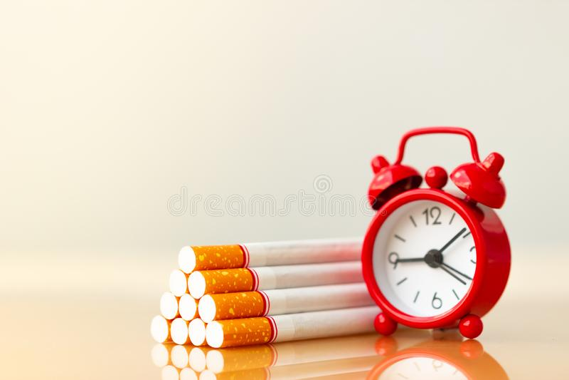 Zigarettenstapel und roter Wecker Welt kein Tabak-Tag Zigaretten- und Familienzahl lizenzfreies stockfoto