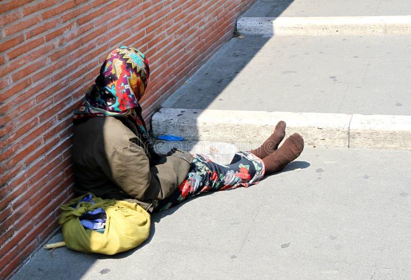 Zigenare med lurid kläder, medan tigga på gatan arkivbild