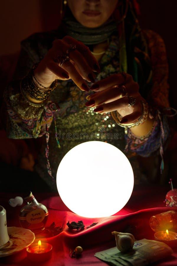 Zigensk kvinna för förmögenhetkassör som rymmer hennes händer ovanför kristallkula arkivfoton