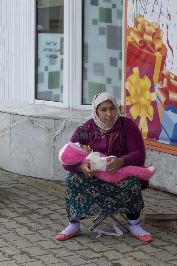Zigeunerin mit einem Kind nahe dem Speicher bitten um Almosen lizenzfreies stockfoto