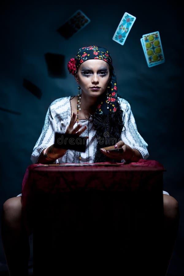 Zigeunervermögenserzähler, der die tarot Karten wirft. stockfotografie