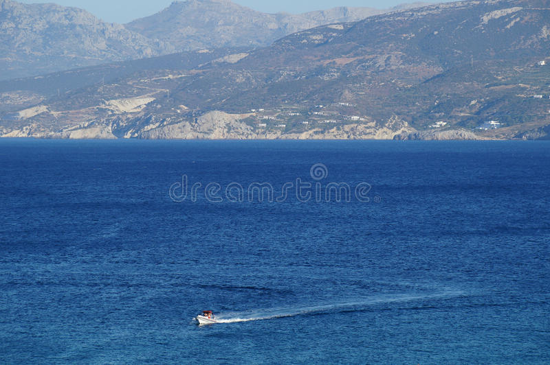 Zigzag. A boat in the sea in front of mountain sea shore of Crete island royalty free stock images