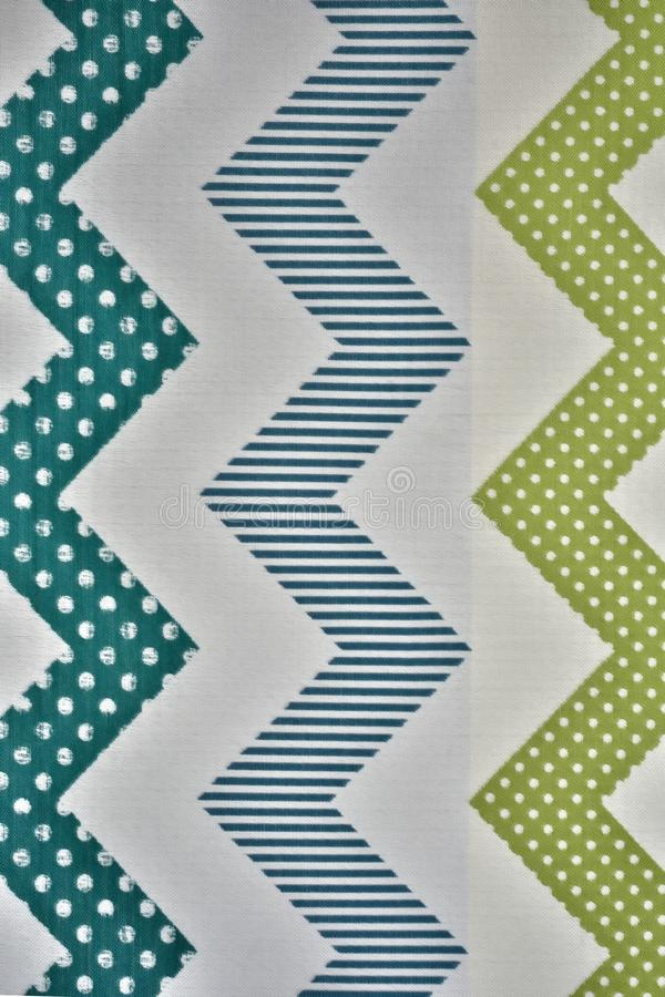 Zigzag lines of various colors, consisting of dots and straight lines on light fabric. In a traditional North African style royalty free stock photo