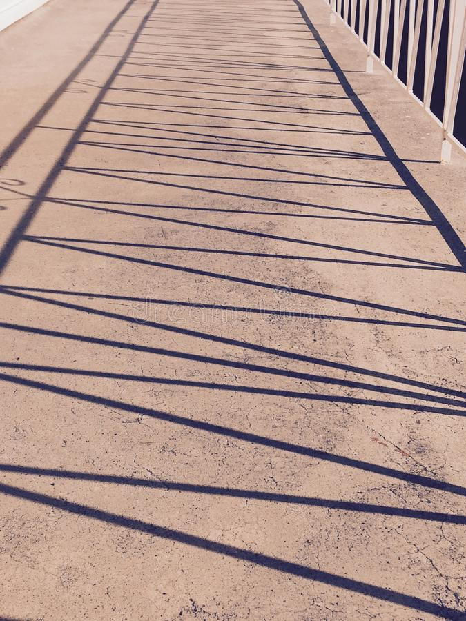 A zigzag pattern of fence shadow. A zigzag pattern on a lime floor with a shadow of a balcony iron fence, black and white stock photos
