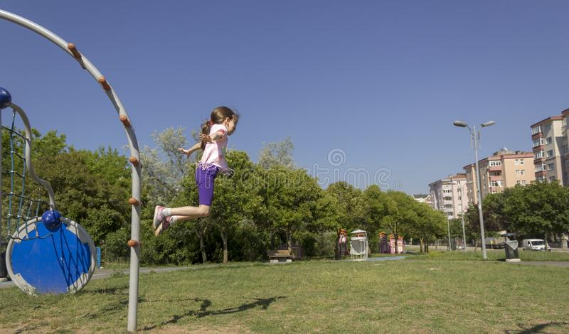 Zij die als sprinkhaan bij speelplaats springen stock foto