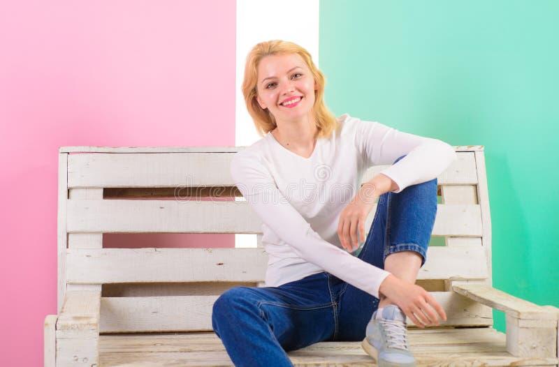 Zij is eenvoudig schitterend Mooie jonge vrouwenglimlach terwijl het zitten op bank tegen roze achtergrond Het meisje verkiest royalty-vrije stock foto's