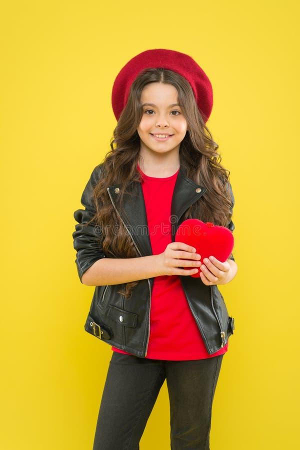 Zij heeft een het houden van hart Aanbiddelijk meisje die rood hart op gele achtergrond houden Leuk klein kind met zacht hart stock fotografie