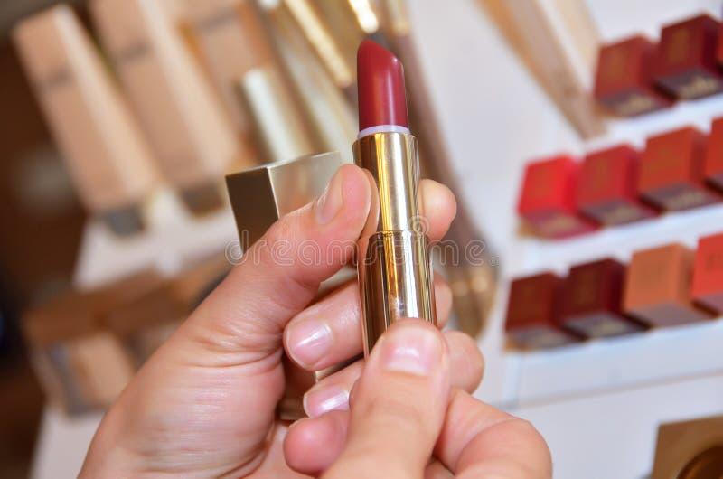 Zij heeft een vrouwelijke rode lippenstift Vrouwelijke hand met rode lippenstift rode kleur en het testen verschillende lippensti stock afbeeldingen