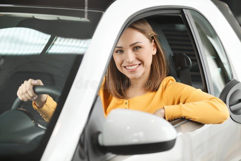 Zij heeft haar droomauto gekocht! Aantrekkelijke jonge vrouwenzitting bij stock foto