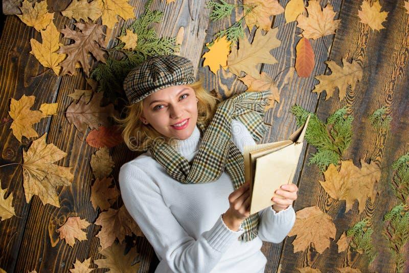 Zij houdt detective van genre Het meisjesblonde legt houten achtergrond met bladeren Vrouwendame in geruite hoed en gelezen sjaal stock foto's