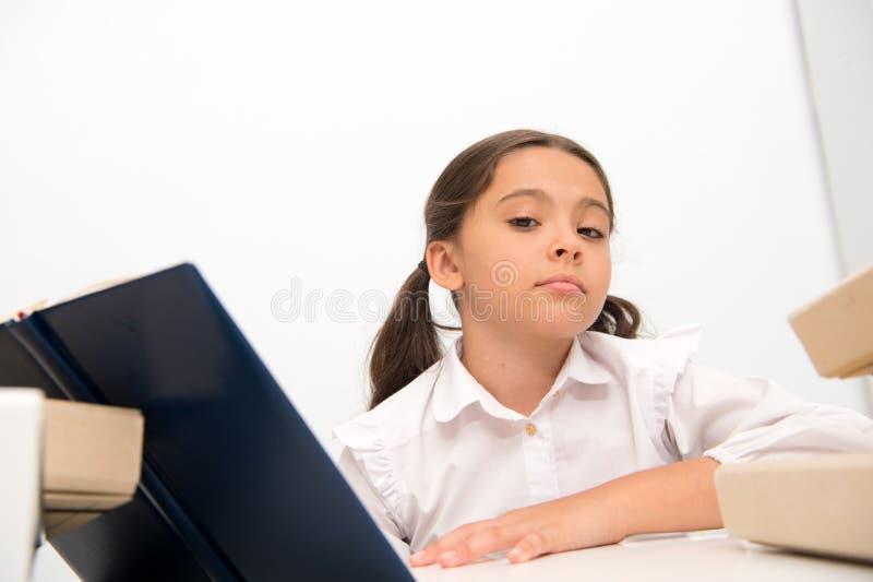 Zij is klaar met haar huistaak Het meisjeskind las boek terwijl lijst witte achtergrond zit En schoolmeisje die bestuderen lezen royalty-vrije stock fotografie