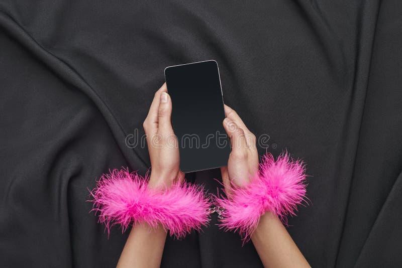 Zij is in uw controle Het wijfje dient roze bonthandcuffs in houdend smartphone op een zwarte zijdestof royalty-vrije stock fotografie