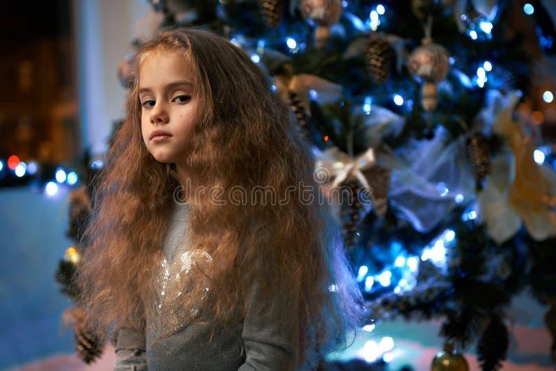 Zij veracht het meisje dichtbij Kerstboom royalty-vrije stock fotografie