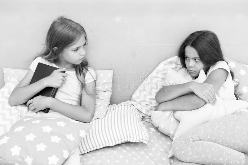 Zij wil niet haar boek delen Het concept van de zustersrivaliteit De kwesties van zustersrelaties Aandeelboek met vriend Kinderen royalty-vrije stock fotografie