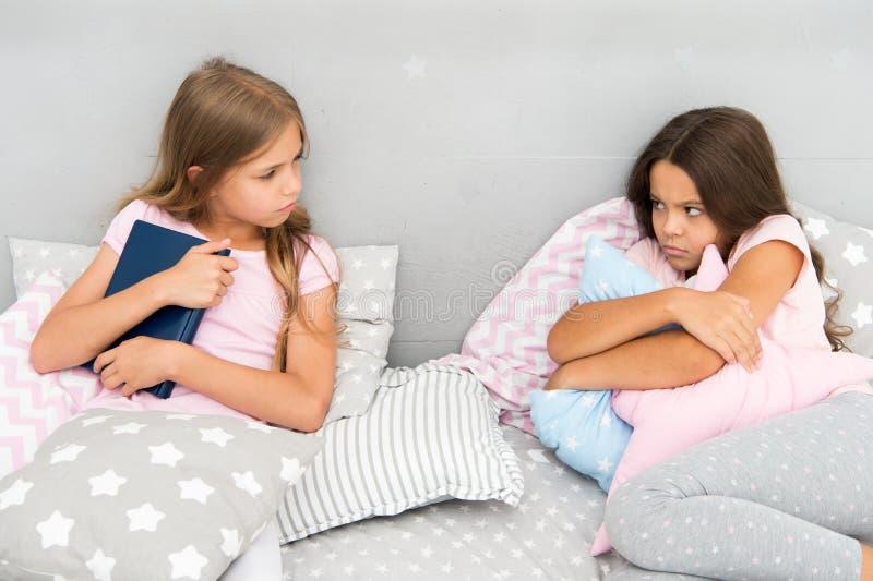 Zij wil niet haar boek delen Het concept van de zustersrivaliteit De kwesties van zustersrelaties Aandeelboek met vriend Kinderen royalty-vrije stock afbeelding