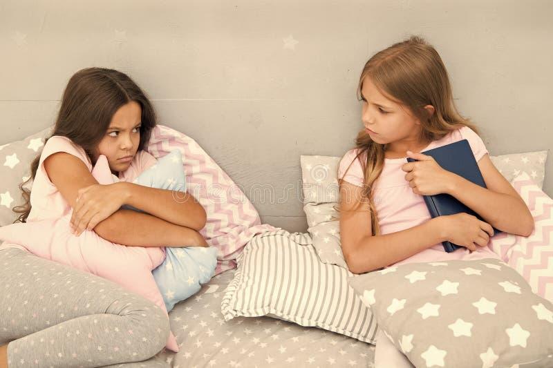 Zij wil niet haar boek delen Het concept van de zustersrivaliteit De kwesties van zustersrelaties Aandeelboek met vriend Kinderen royalty-vrije stock foto