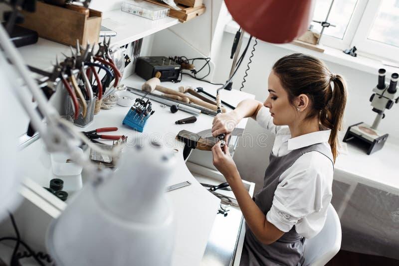 Zij is zo hartstochtelijk over haar project Zijaanzicht van jonge vrouwelijke juwelier die aan een nieuw juwelenproduct bij haar  royalty-vrije stock afbeelding