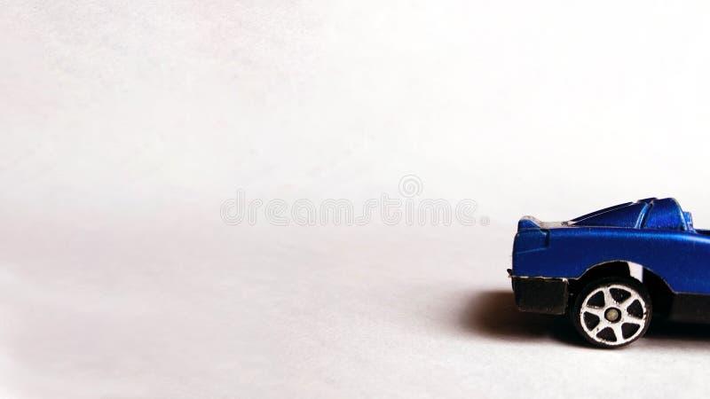 Zijaanzicht dat van rug van blauwe stuk speelgoed auto op schone achtergrond wordt geschoten royalty-vrije stock foto's